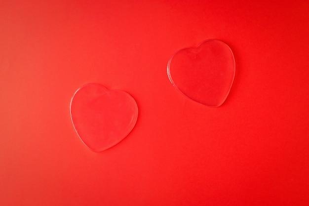 Deux coeurs transparents sur fond rouge vif. un symbole d'amour et de vie.
