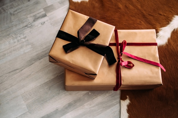 Deux coffrets cadeaux artisanaux reposent sur le sol près du tapis. concept de cadeau. ambiance de noël.