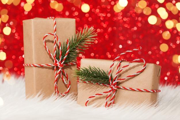 Deux coffrets cadeaux enveloppés de ruban sur une surface de paillettes rouges