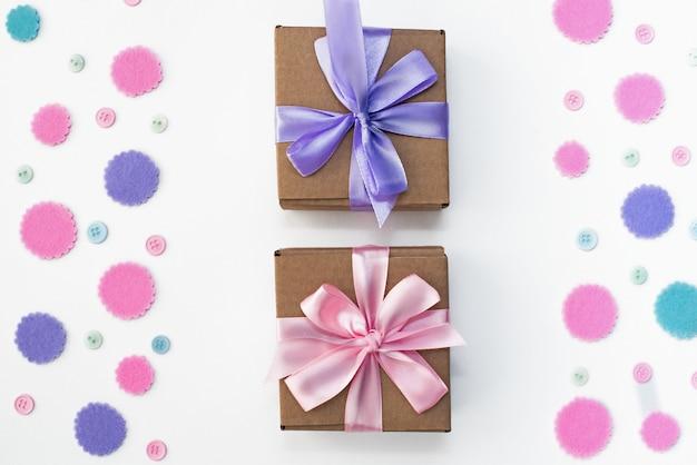 Deux coffrets cadeaux sur fond festif de confettis pastel.