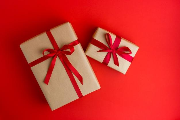 Deux coffrets cadeaux marron avec des rubans rouges sur fond rouge. style plat. cadeau pour noël, vacances ou anniversaire.