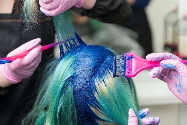 Deux coiffeurs professionnels portant un gant de protection utilisant une brosse rose tout en appliquant de la peinture bleue sur une femme aux cheveux émeraude, pendant le processus de teinture des cheveux dans une couleur unique dans un salon de beauté.