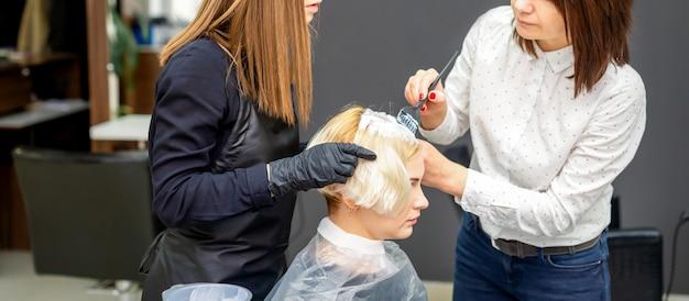 Deux coiffeurs teinture des cheveux de femme