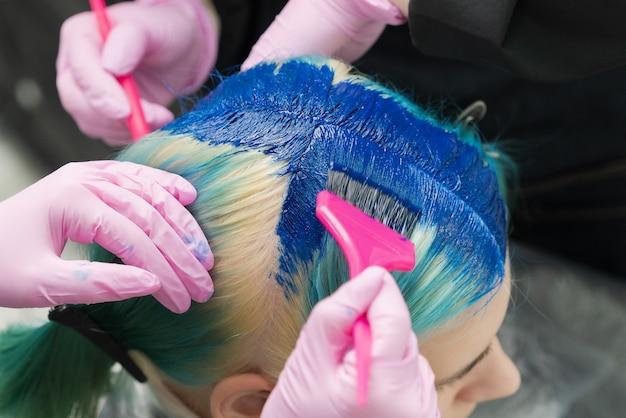 Deux coiffeurs utilisant une brosse rose tout en appliquant de la peinture bleue à une cliente avec une couleur de cheveux émeraude pendant le processus de teinture de ses cheveux dans une couleur unique