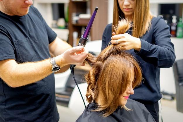 Deux coiffeurs utilisant un fer à friser sur les longs cheveux bruns des clients dans un salon de beauté.