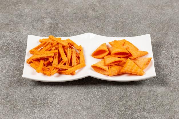 Deux collations chaudes. chips sur plaque blanche.