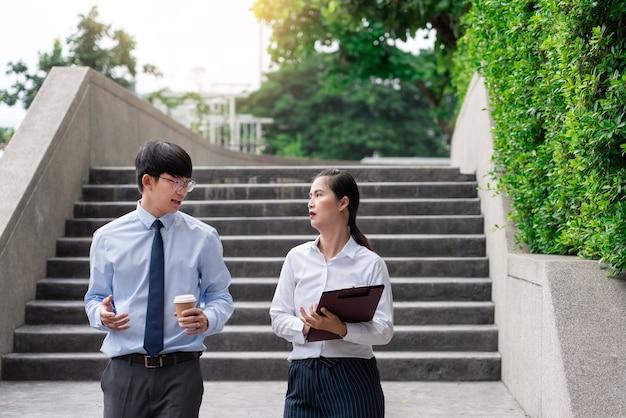 Deux collègues d'affaires discutant d'un nouveau projet de réunion d'affaires à l'extérieur du bureau en milieu urbain.