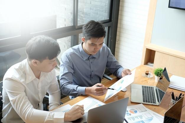Deux collègues asiatiques travaillant ensemble sur un ordinateur portable et des documents à un bureau dans une salle de réunion.