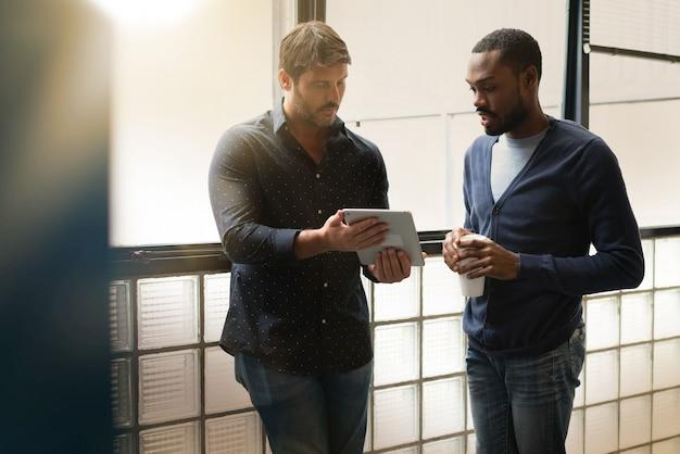 Deux collègues debout ensemble dans un bureau moderne, passant en revue des idées sur une tablette