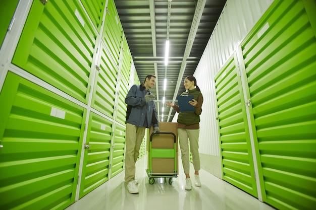 Deux collègues discutent de la livraison de colis pendant qu'ils travaillent dans un entrepôt