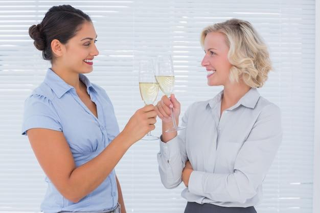 Deux collègues joyeux cliquent leurs flûtes de champagne au travail