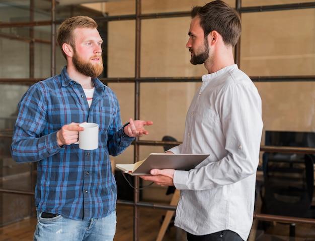 Deux collègues masculins discutant entre eux sur le lieu de travail