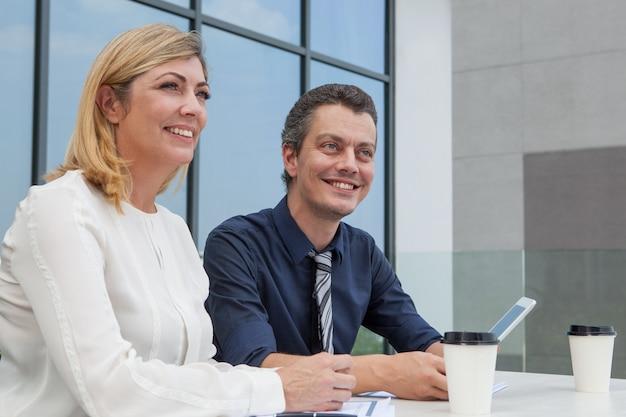 Deux collègues masculins et féminins souriants travaillant dans un café en plein air.