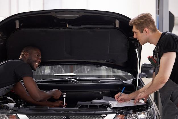 Deux collègues mécaniciens automobiles discutent de ce qu'il faut faire