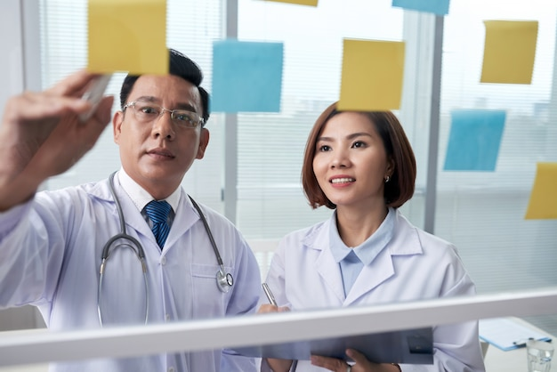 Deux collègues médicaux examinant les autocollants de mémoire sur la planche de verre