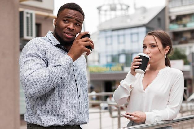 Deux collègues prenant un café ensemble au travail pendant la pandémie