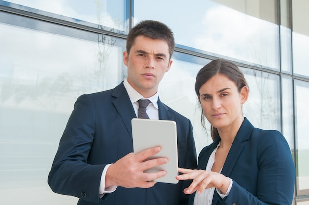 Deux collègues sérieux utilisant une tablette pendant une pause de travail en plein air