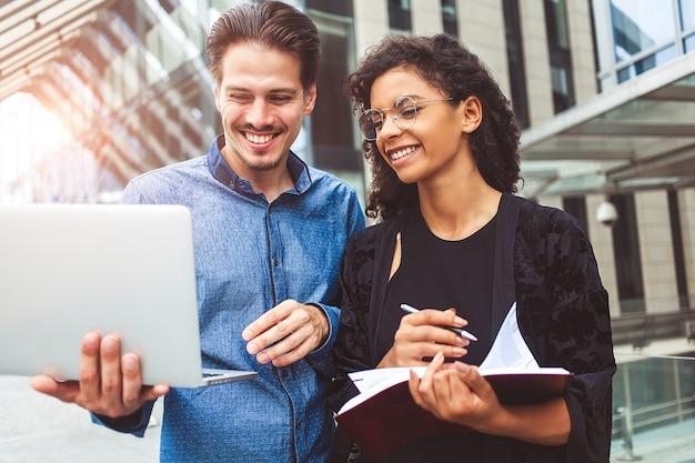 Deux collègues souriants discutent dans la rue pendant la pause déjeuner près du centre d'affaires