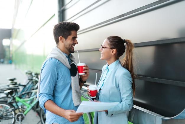 Deux collègues souriants habillés élégamment debout à l'extérieur et tenant des documents tout en buvant du café.
