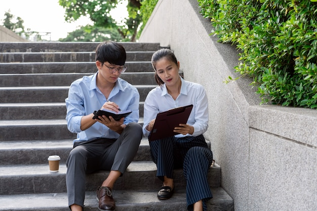 Deux collègues de travail asiatiques à l'extérieur des immeubles de bureaux discutent et commentent leur travail.