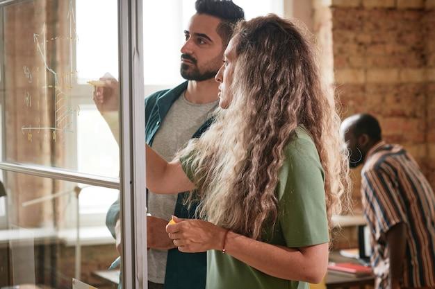 Deux collègues de travail dessinant des graphiques ensemble sur un mur de verre et en discutant lors de la présentation au bureau