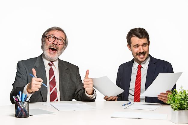 Les deux collègues travaillant ensemble au bureau sur blanc.