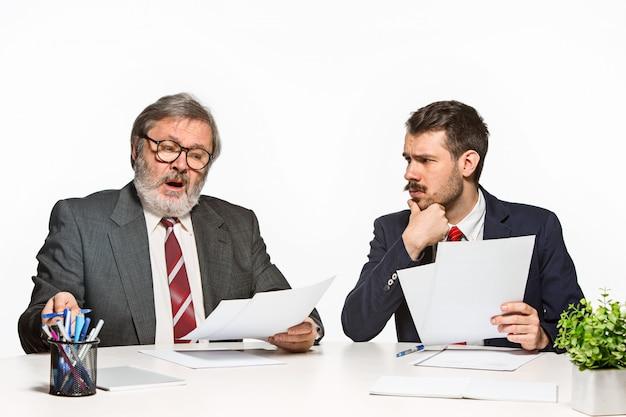 Les deux collègues travaillant ensemble au bureau sur studio blanc