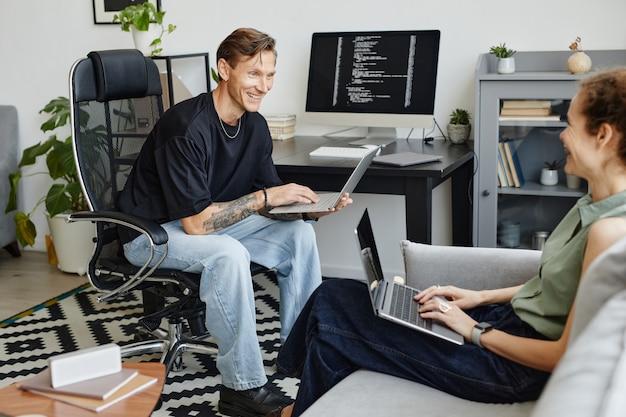 Deux collègues travaillant sur des ordinateurs et discutant ensemble de logiciels informatiques dans la pièce
