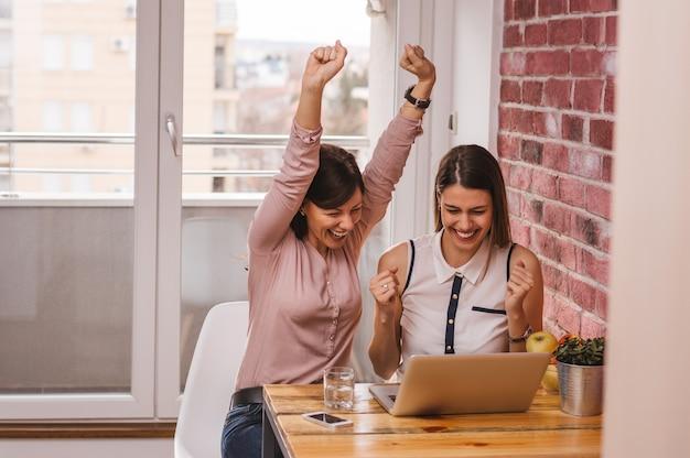 Deux colocataires excités lisant de bonnes nouvelles en ligne avec un ordinateur portable