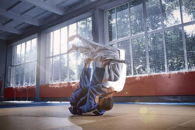 Deux combattants de judo montrant des compétences techniques tout en pratiquant les arts martiaux dans un club de combat. les deux hommes en uniforme. combat, karaté, entraînement, arts, athlète, concept de compétition