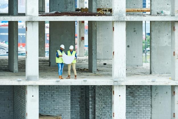 Deux constructeurs détenant des plans de construction