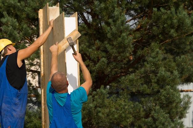 Deux constructeurs érigeant des panneaux muraux en bois isolés sur une nouvelle maison en les alignant soigneusement pour l'installation