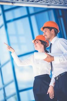 Les deux constructeurs avec un geste de papier sur le fond du bâtiment moderne