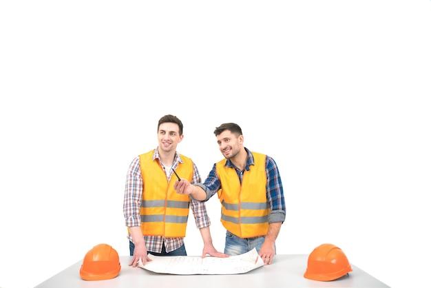 Les deux constructeurs avec un papier sur une table discutent sur le fond blanc