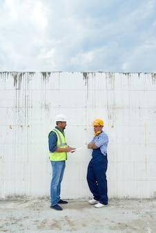 Deux, construction, ouvriers, discuter, bâtiment