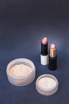 Deux conteneurs de poudre de fard à joues beige et de rouges à lèvres sur fond gris