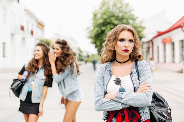 Deux copines en arrière-plan commérages sur le troisième adolescent avec maquillage et coiffure en détournant les yeux avec tristesse.