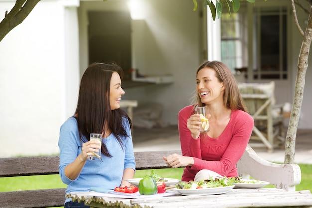 Deux copines assises dehors en train de déjeuner