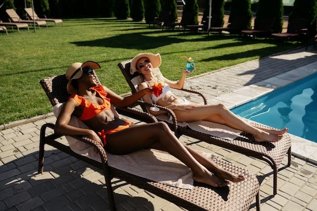 Deux copines boivent des cocktails sur des transats au bord de la piscine. des gens heureux s'amusant pendant les vacances d'été, une fête de vacances au bord de la piscine à l'extérieur. loisirs femmes