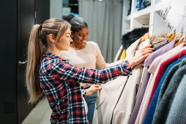 Deux copines choisissant des vêtements en boutique