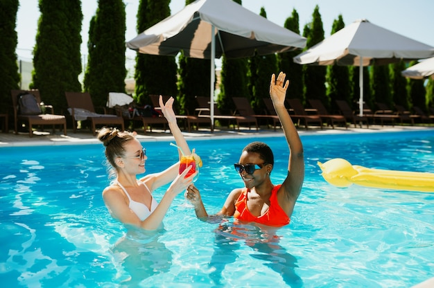 Deux copines avec des cocktails nagent dans la piscine
