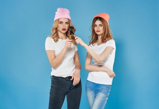 Deux copines dans des vêtements à la mode maquillage fond bleu glamour