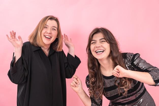 Deux copines gaies rient sincèrement sur fond rose.