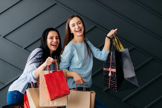 Deux copines joyeuses tenant des sacs à provisions dans leurs mains