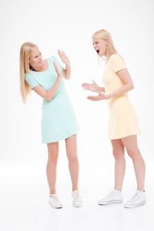 Deux copines jurent. isolé sur un mur blanc.