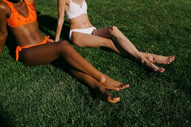 Deux copines en maillot de bain bronzer sur l'herbe