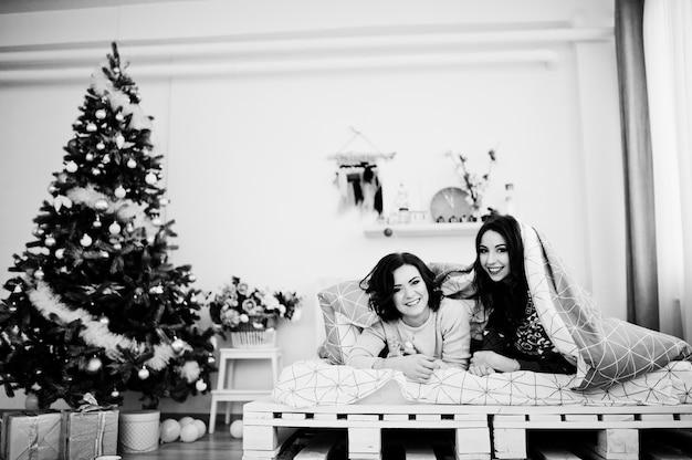 Deux copines portent des chandails d'hiver s'amusant sur un lit dans une chambre avec des décorations de noël.