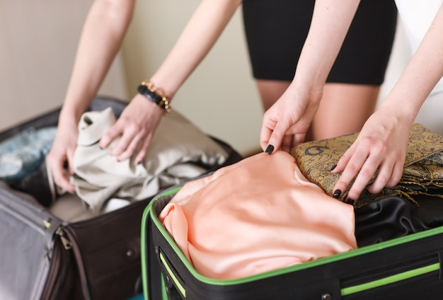 Deux copines ramassent une valise dans une chambre d'hôtel.