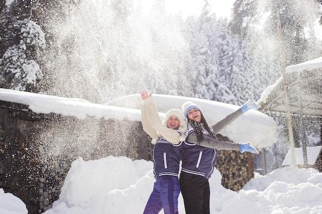 Deux copines s'amusent et profitent de la neige fraîche par une belle journée d'hiver