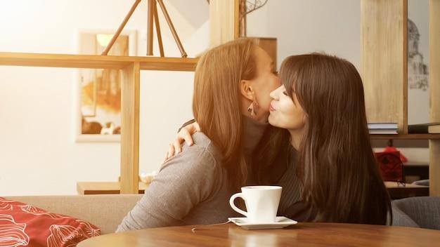 Deux copines se rencontrent au café et s'embrassent, la lumière du soleil